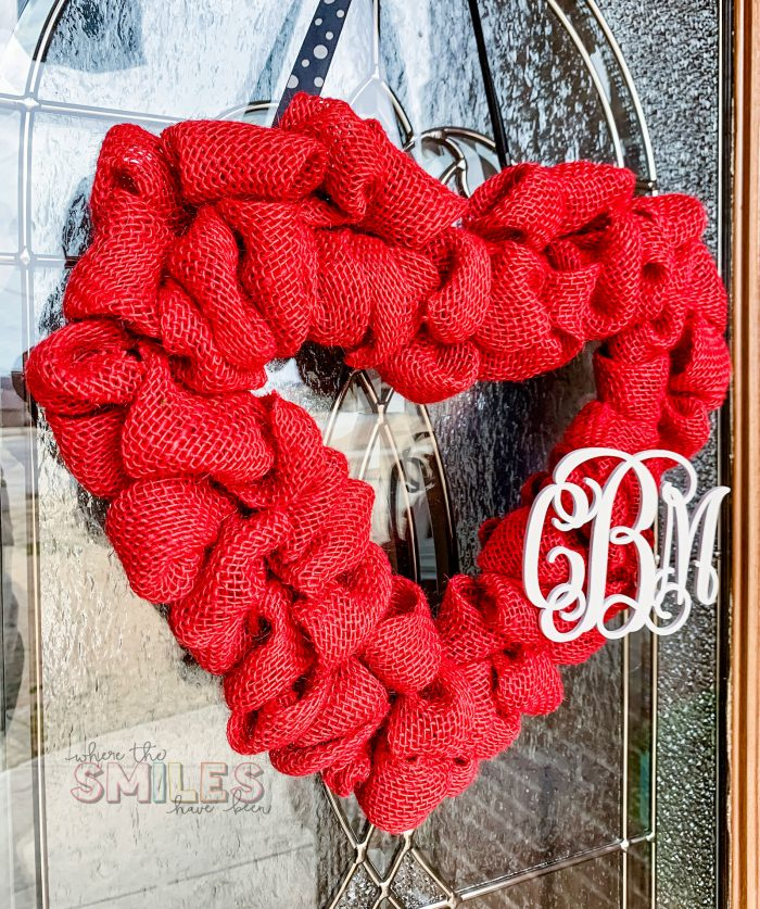 Side angle of red burlap heart Valentine's Day wreath with white couple's monogram hanging on glass door