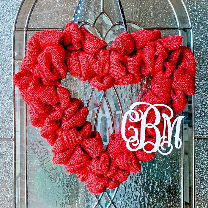 Red burlap heart Valentine's Day wreath with white couple's monogram hanging on glass door