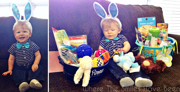 Smiling toddler boy wearing bunny ears sitting next to an Easter basket.