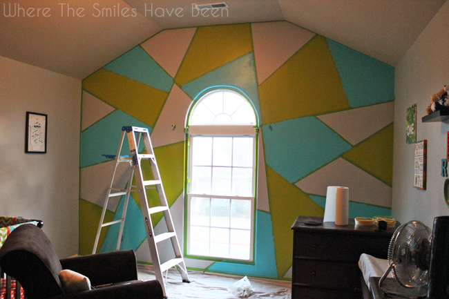 Accent wall with green and blue paints added to random shapes.