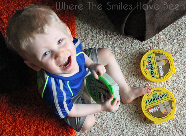 Happy toddler boy smiling at the camera while playing with Frog Tape rolls.