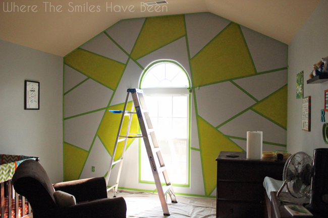 Accent wall with green paint added to random shapes.