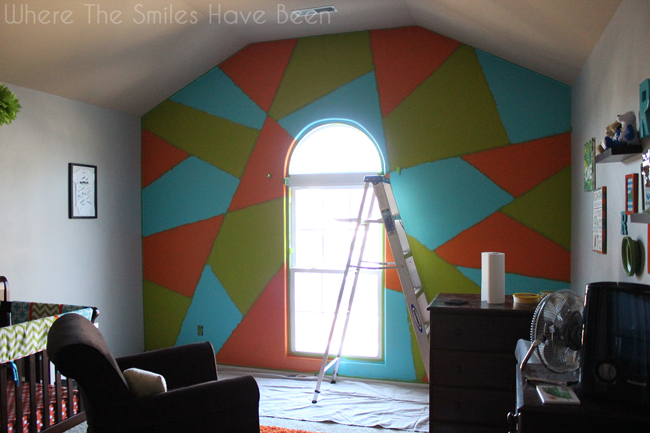Accent wall with blue, green, and orange paint added to random shapes, before removing the painter's tape to reveal gray lines.
