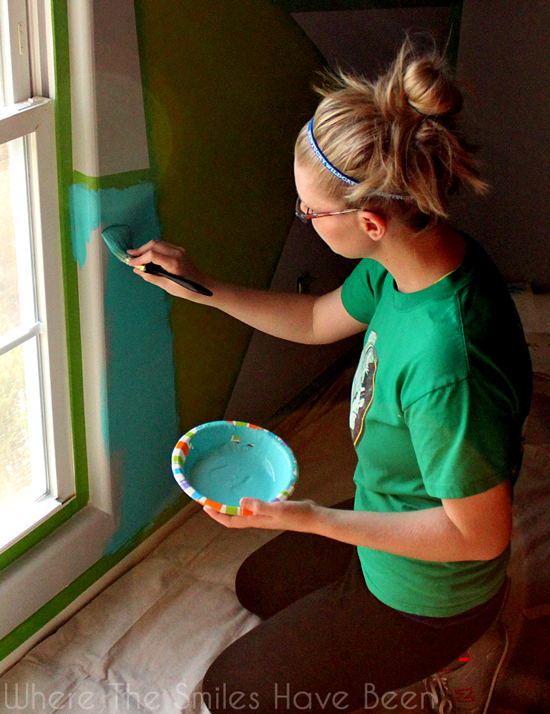Blond young woman painting blue paint on an accent wall.