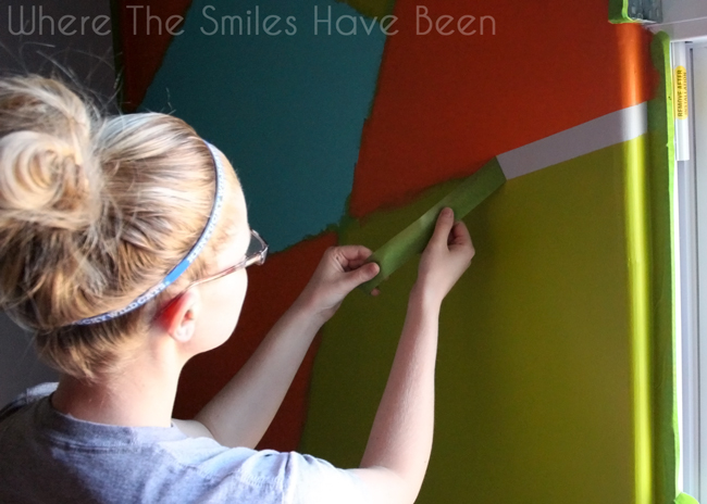 Young blond woman peeling away painter's tape to reveal gray lines.