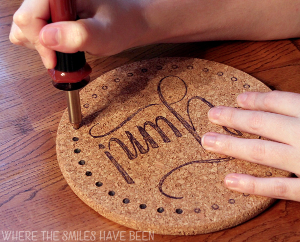 Hands holding a wood burning tool and burning a drawn design into cork.