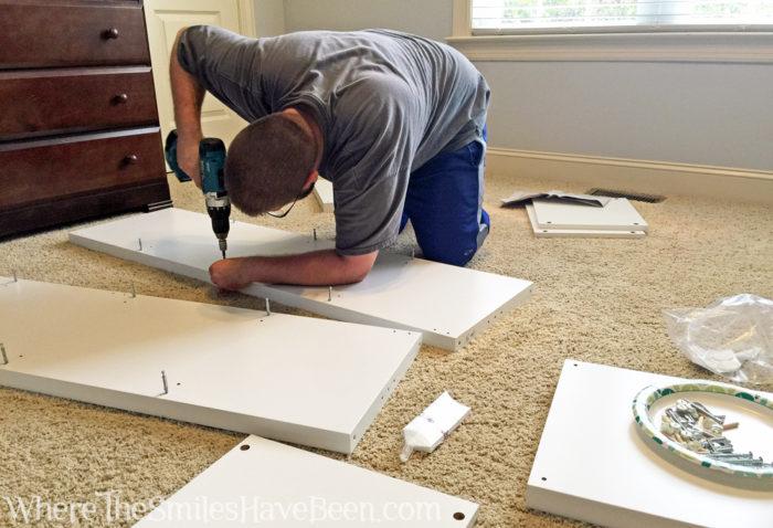 Assembling a white IKEA Kallax shelf unit using a power drill.