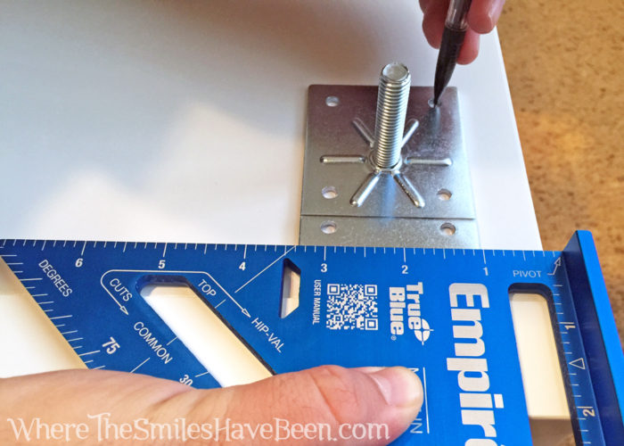 Using a blue rafting square to mark locations for screwing in IKEA Capita legs onto a Kallax shelf.