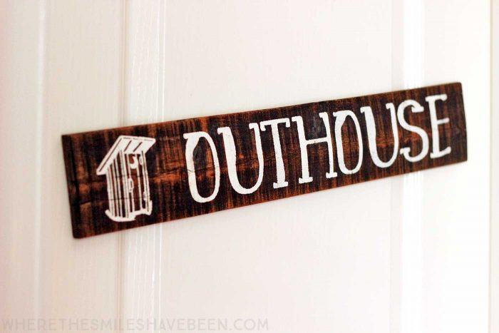 What a cute sign for a bathroom door in a rustic woodland nursery! Take a tour of this navy & orange modern woodland nursery!   Where The Smiles Have Been