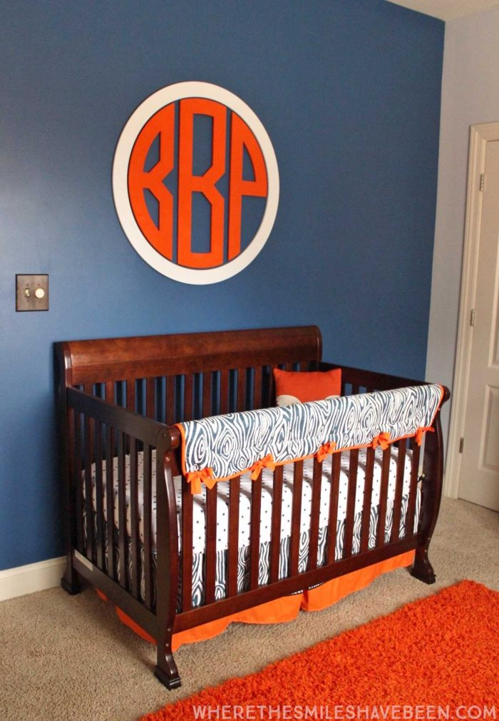 LOVE this giant circle monogram above the crib! It's perfect for a baby boy's room! Take a tour of this Navy & Orange Modern Woodland Nursery!   Where The Smiles Have Been