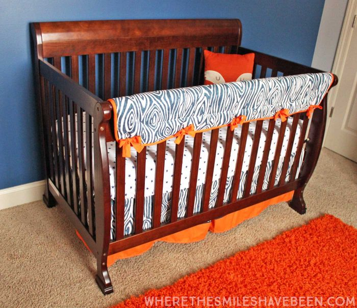 LOVE this woodgrain crib rail guard and crib skirt! It's perfect for a rustic or woodland nursery! Take a tour of this Navy & Orange Modern Woodland Nursery!   Where The Smiles Have Been