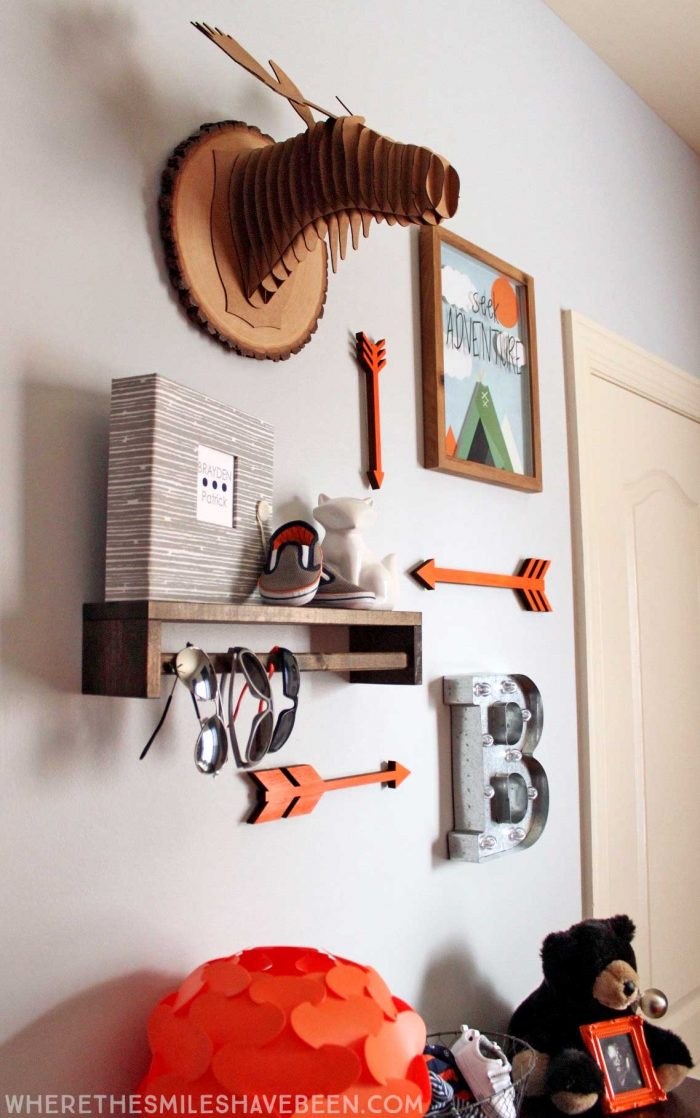 LOVE this mini gallery wall in a baby's room! That moose head and shelf are great! Take a tour of this navy & orange modern woodland nursery!   Where The Smiles Have Been