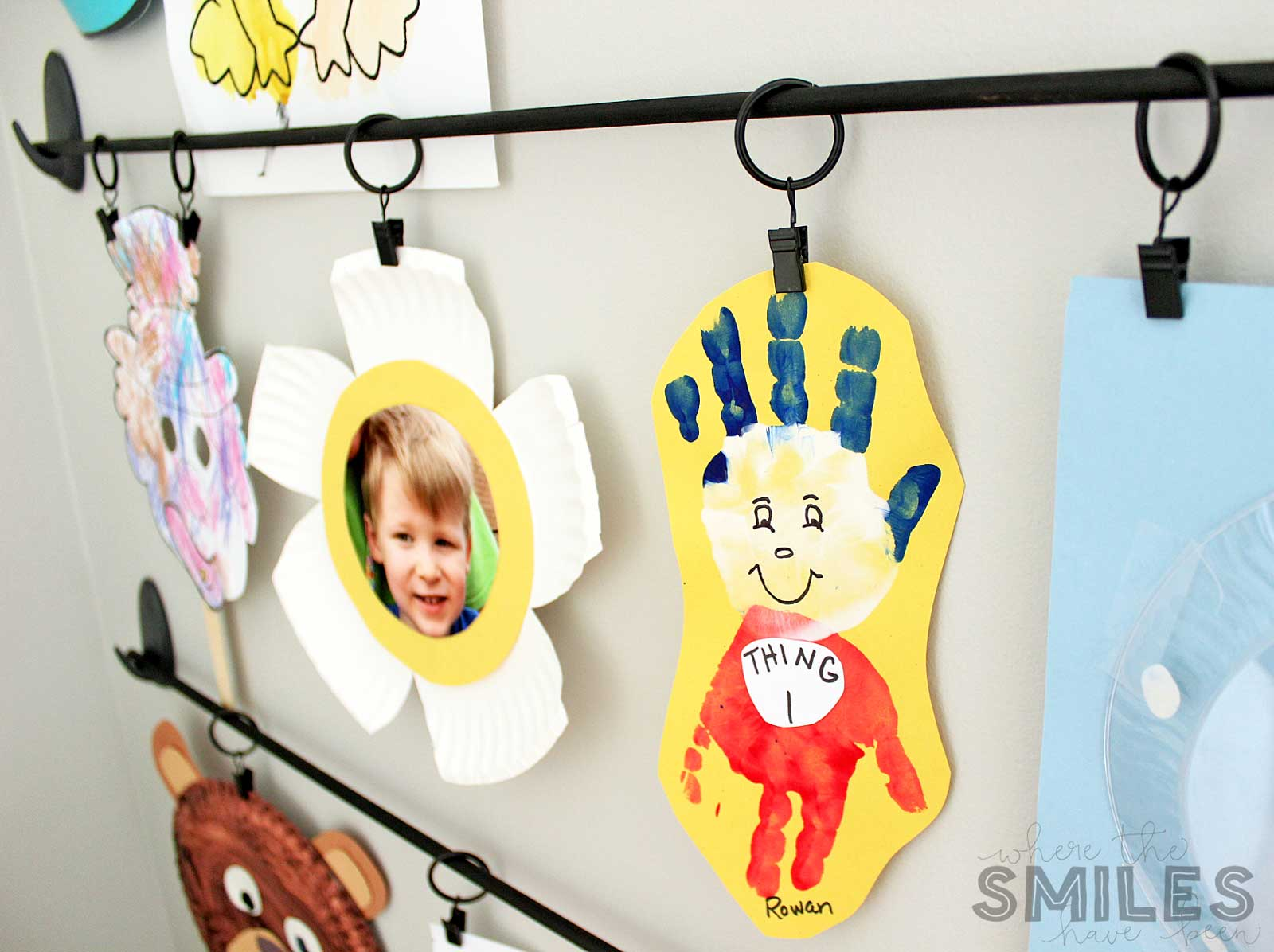 Easy DIY Kids Art Display with kid's artwork hanging from curtain clips.