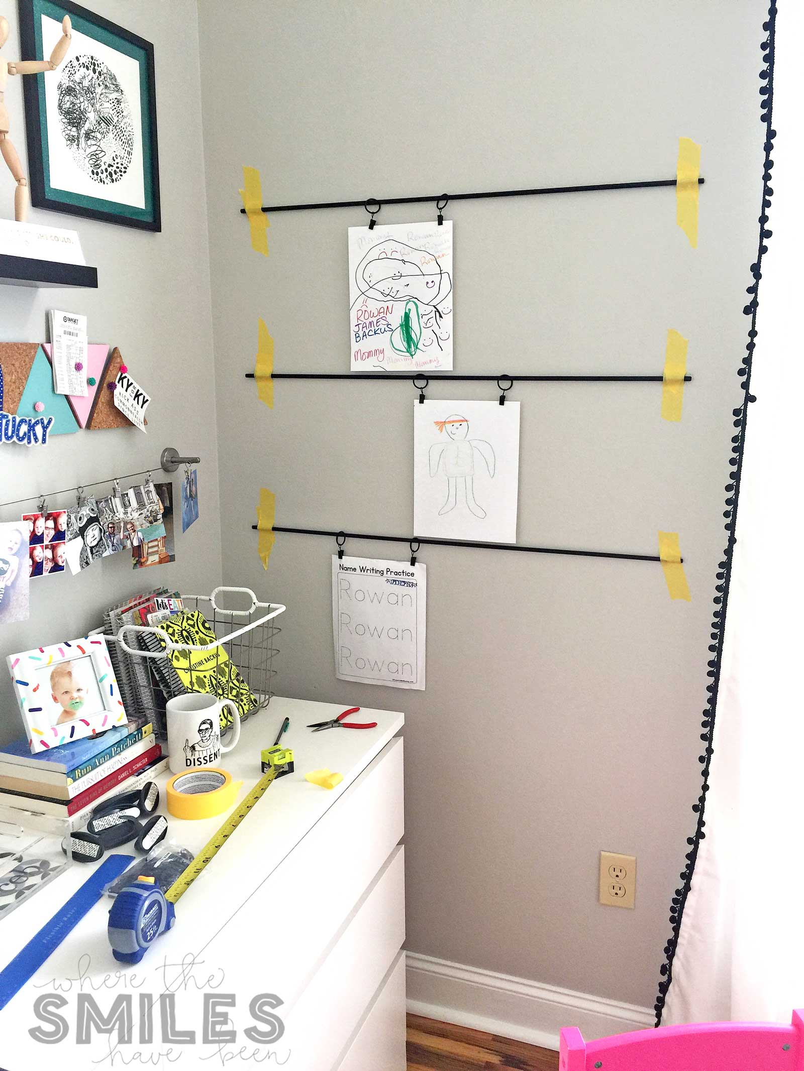 Process shot of kids art display rods being hung with painter's tape.
