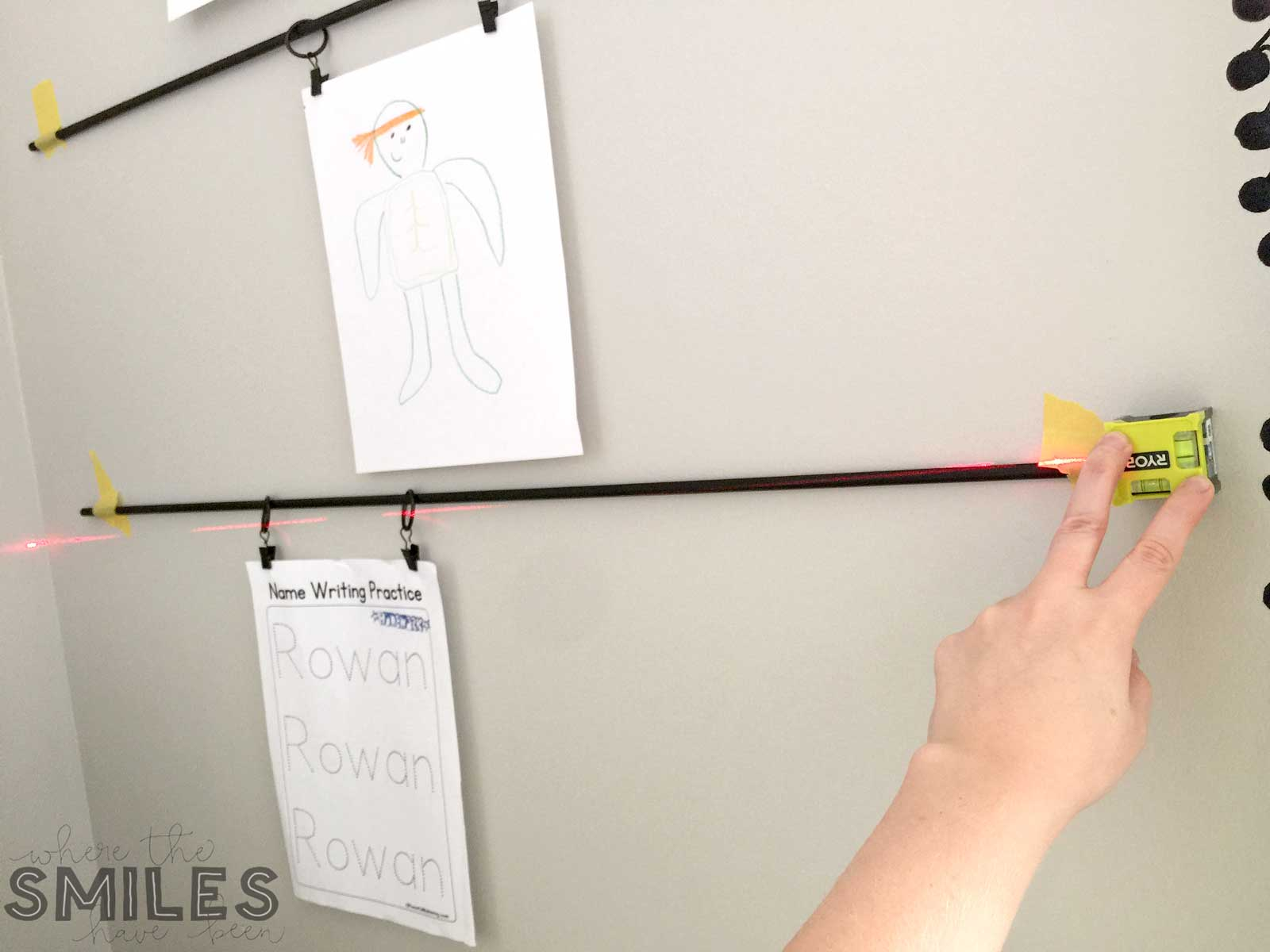 Using a laser level to hang kids art display.