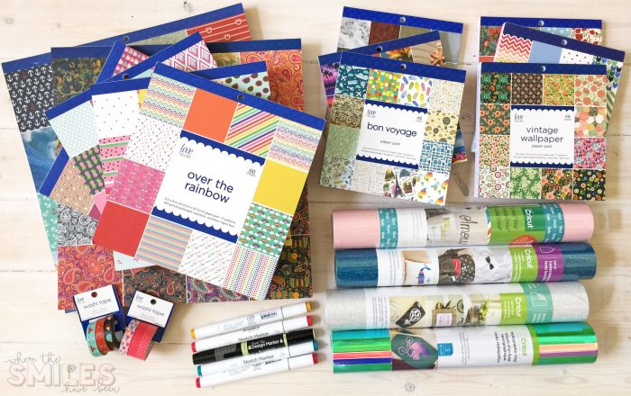 Craft supplies of scrapbook paper, vinyl, markers, and washi tape.