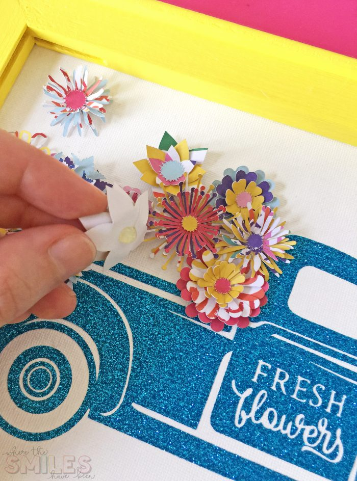 Gluing paper flowers to a reverse canvas sign.