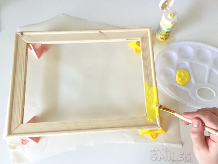 Painting a bare canvas frame with yellow craft paint.