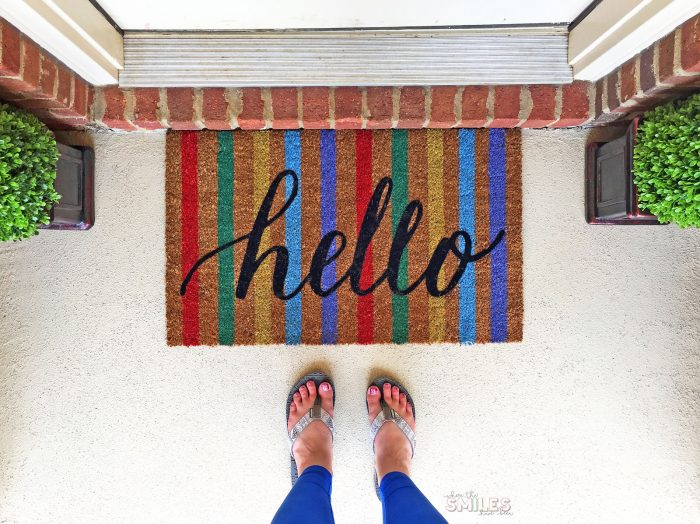 """Colorful doormat that says """"hello"""" on repainted porch."""