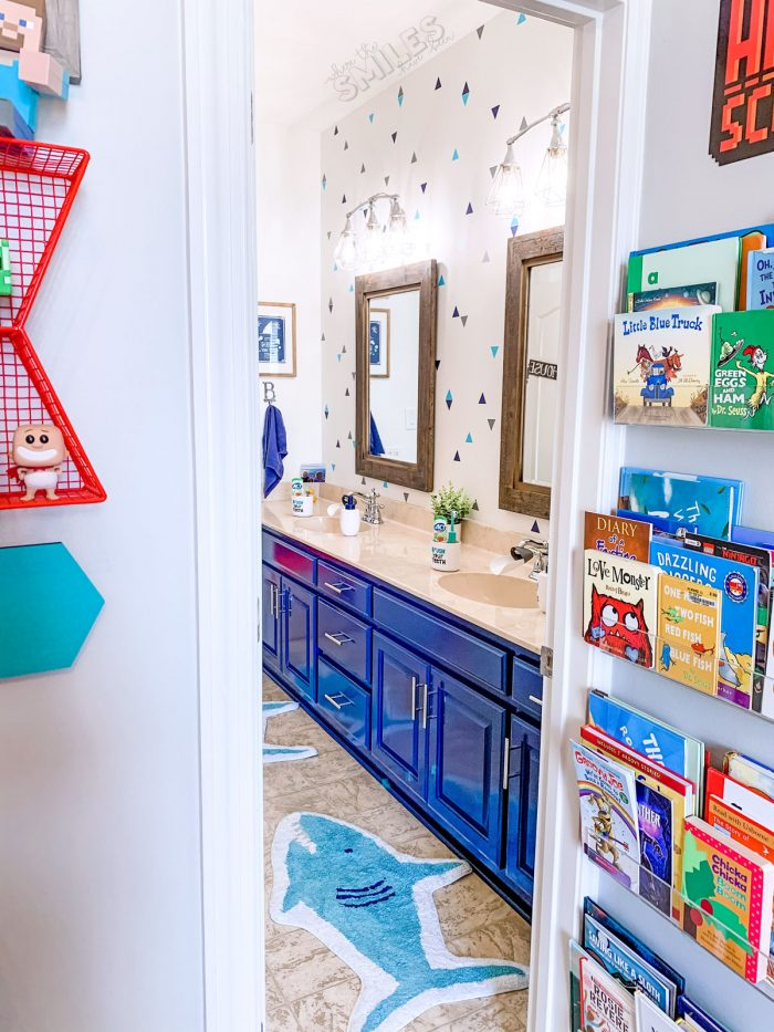 shark kids bathroom with blue cabinets and triangle faux wallpaper.