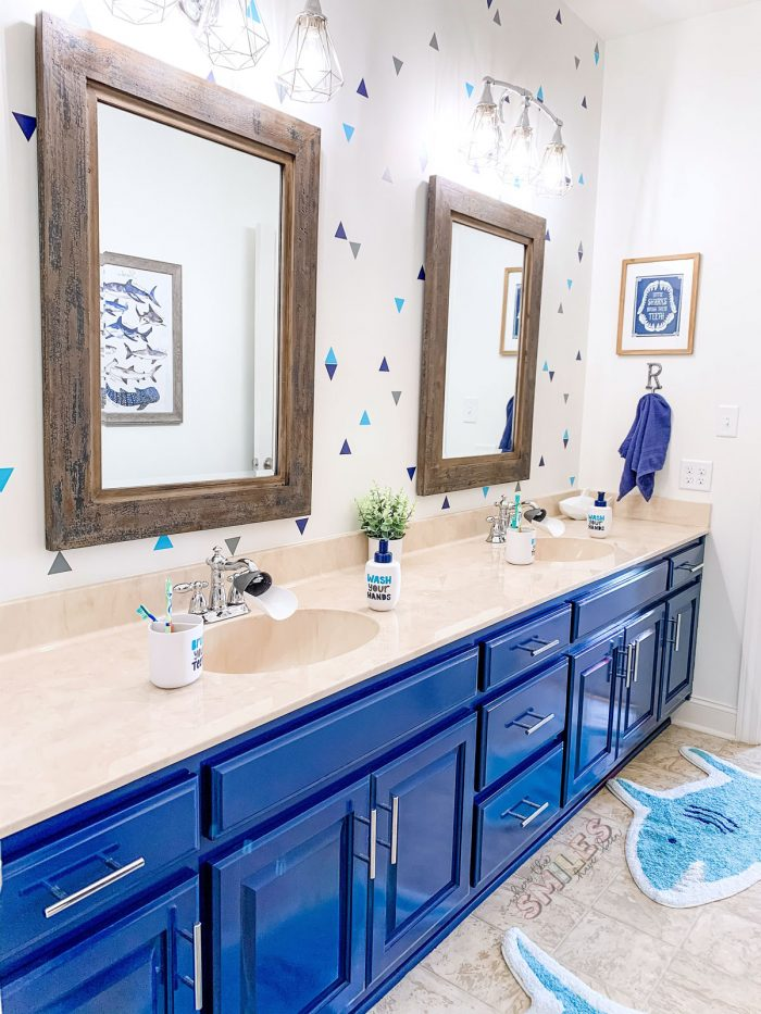 kids bathroom with blue painted cabinets and faux wallpaper.