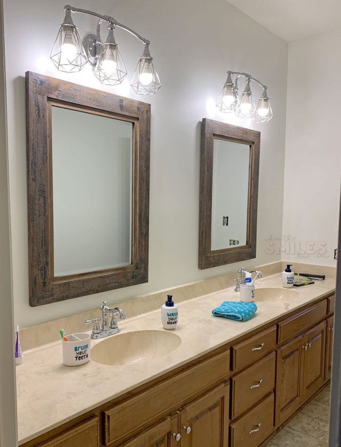 Jack-and-Jill bathroom sink area with plain white walls and oak cabinets.