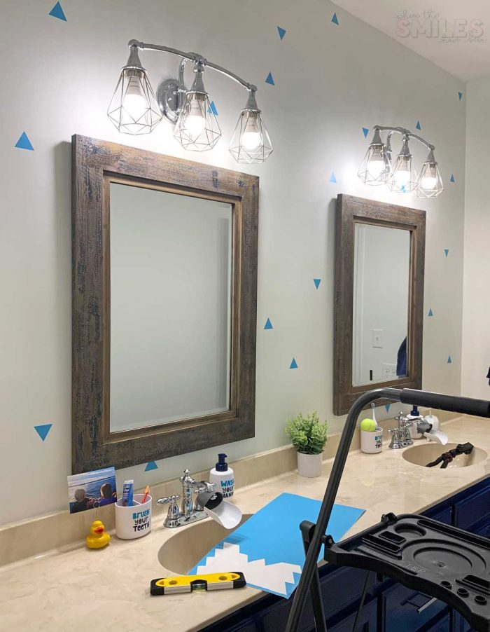 This kids bathroom makeover is SO COOL and was SO EASY! Kids Bathroom Makeover: Shark Attack! | Where The Smiles Have Been #bathroom #bathroommakeover #kidsbathroom #kidsroom #shark #sharkbathroom #paintedcabinets #bluebathroom #bluecabinets #vinyl #indoorvinyl #vinylwallpaper #wallpaper #makeover #easymakeover #DIYmakeover