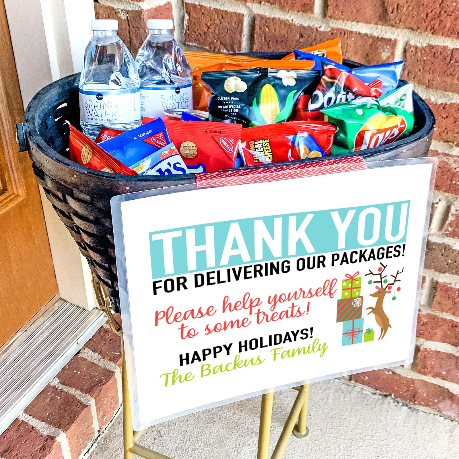Basket on porch filled with free snacks and drinks for delivery drivers and a free printable sign.